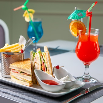 Fast food with sandwich, french fries, red cocktail, fork and knife on table, side view.