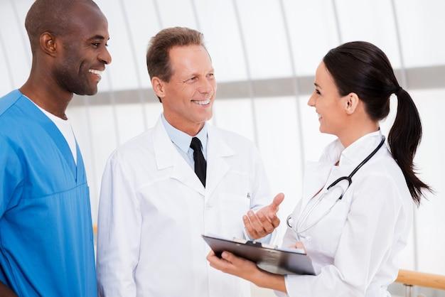 速い会議。女性がクリップボードを持って笑っている間に何かを話し合う自信のある3人の医師