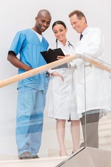 빠른 회의. 계단에 서서 무언가를 논의하는 세 명의 자신감 있는 의사