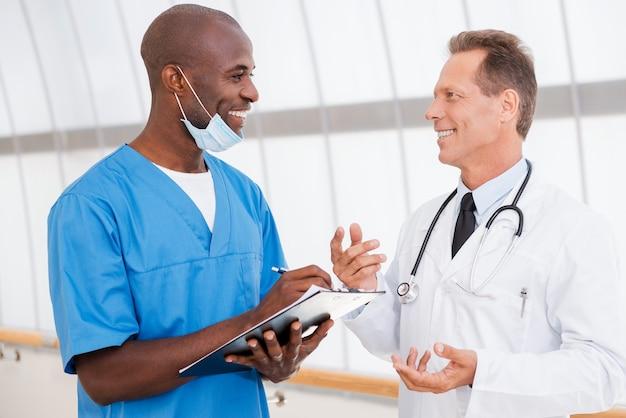 速い会議。自信を持って2人の医師が何かについて話し合い、1人がクリップボードを持って笑っている