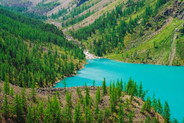 Fast mountain creek flows into azure mountain lake in valley