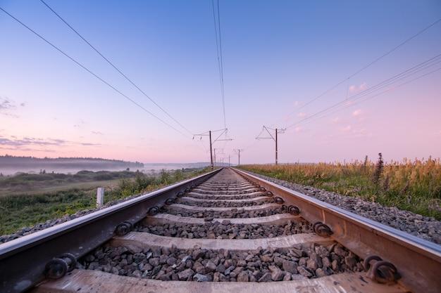 線路上を高速で移動します。コンセプト、鉄道配達、旅行、スピード。夜明けまたは日没時に空の鉄道。