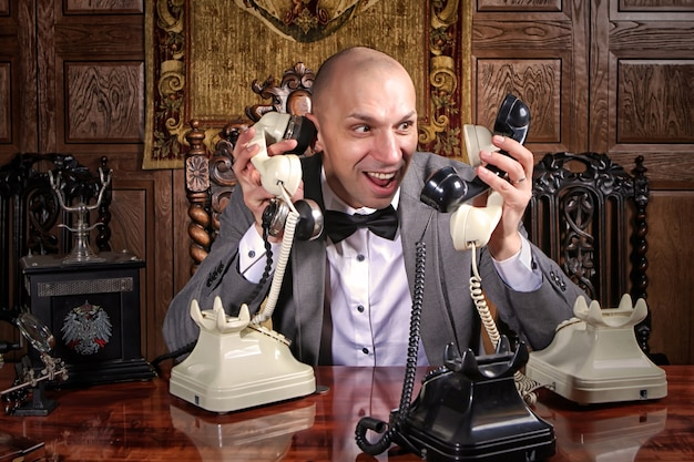 급변하는 절망적인 사업가 쇼맨은 사무실에서 일하고 많은 전화를 걸고 많은 핸드셋을 유지합니다. 비즈니스 관리 개념입니다. 스트레스를 받는 남자는 한 번에 많은 전화로 이야기합니다. 저작권 공간