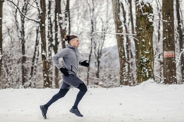 Fast runner running in forest on snowy winter day. healthy lifestyle, winter fitness