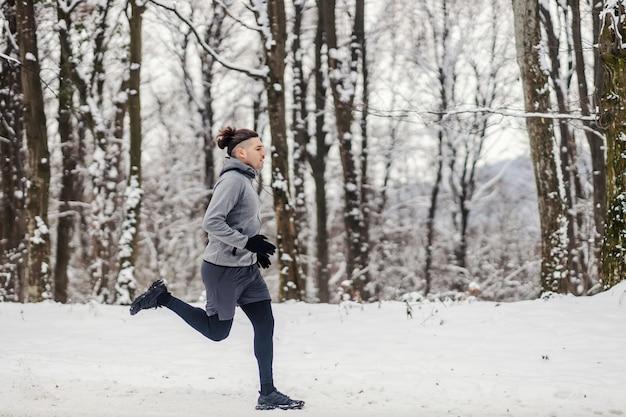 눈 덮인 겨울 날 숲에서 달리는 빠른 주자. 건강한 라이프 스타일, 겨울 피트니스, 유산소