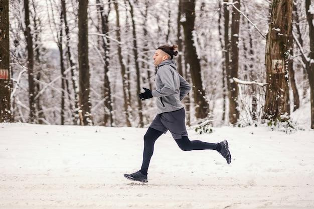 눈 덮인 겨울 날 숲에서 달리는 빠른 주자. 건강한 생활 방식, 겨울 피트니스, 유산소