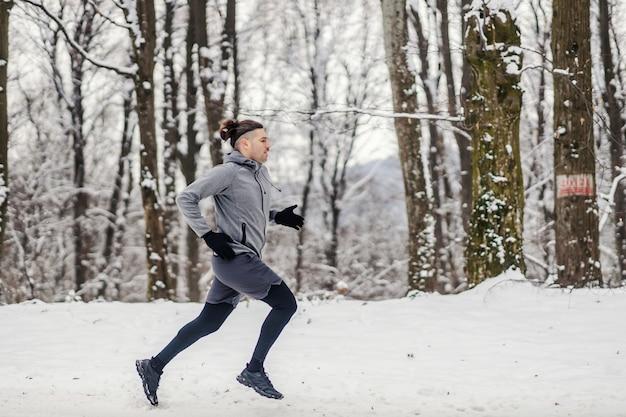 雪の降る冬の日に森の中を走る速いランナー。健康的なライフスタイル、冬のフィットネス