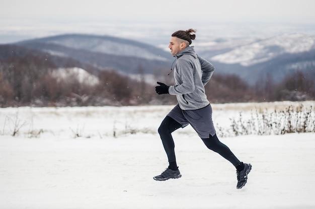 雪の降る冬の日に自然の中で走る速いランナー。健康的なライフスタイル、冬のフィットネス