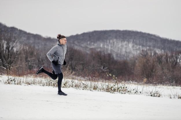 雪の降る冬の日に自然の中で走る速いランナー。
