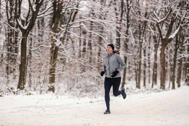 눈 덮인 겨울 날 숲에서 달리는 빠른 주자. 건강한 습관, 야외 피트니스, 쌀쌀한 날씨