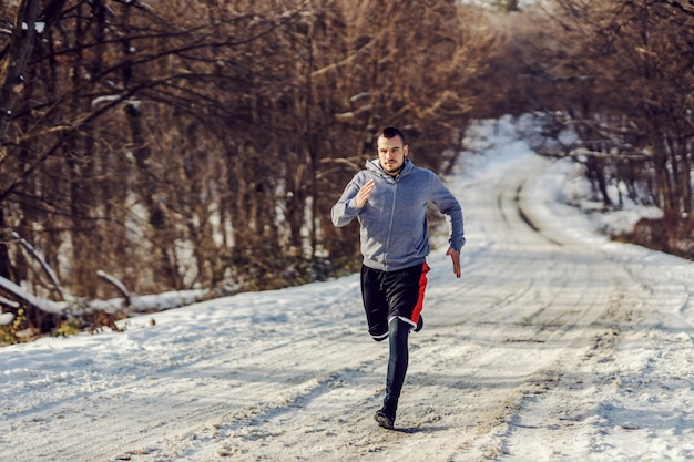 Fast runner running on snowy path in nature at sunny winter day