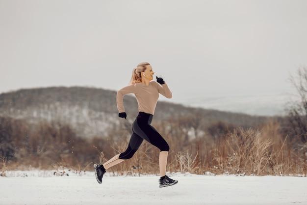 눈 덮인 겨울 날 자연 속에서 빠르게 달리는 빠른 스포츠우먼. 유산소 운동, 건강한 습관, 겨울 스포츠