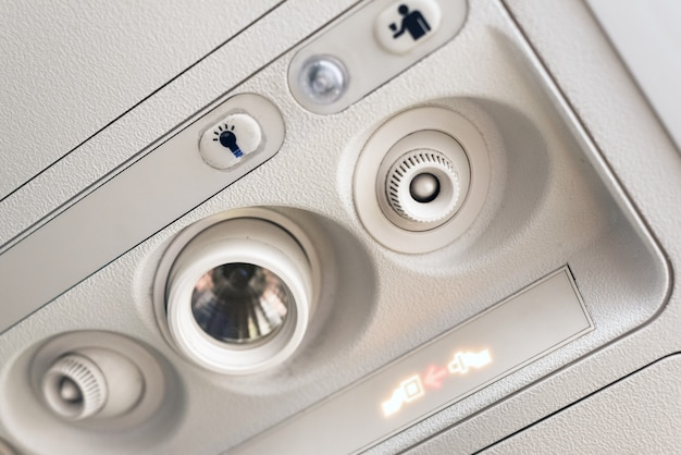 Fasten seat belt light and console panel at the air conditioner above the seat in cabin of low cost commercial airplane.