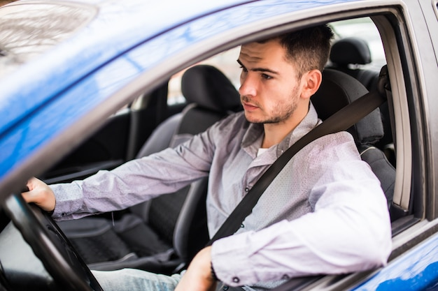 カーシートベルトを締めます。運転中の若い男の安全ベルトの安全性