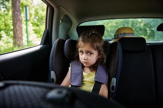 車内のチャイルドシートに小さな女の子を固定しました。車内でのお子様の安全な移動。