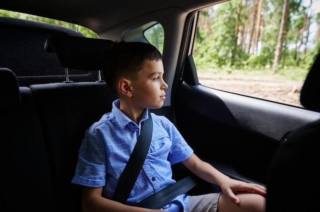 セーフティカーブースターシートに座って、車で旅行中に窓の外を見ている固定された10代の少年