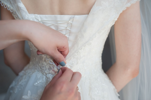 Fastening the dress, button fastening on the bride's dress, bride's fees, wedding dress