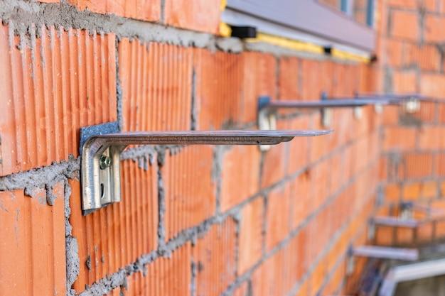 건설 중인 집의 벽돌 벽에 단열재 고정. 고정용 피팅 설치. 선택적 초점입니다.