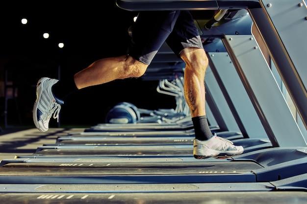 ジムの焦点でトレッドミルで走っているスポーツウェアの運動選手のより速くそしてより速く切り取られたショット