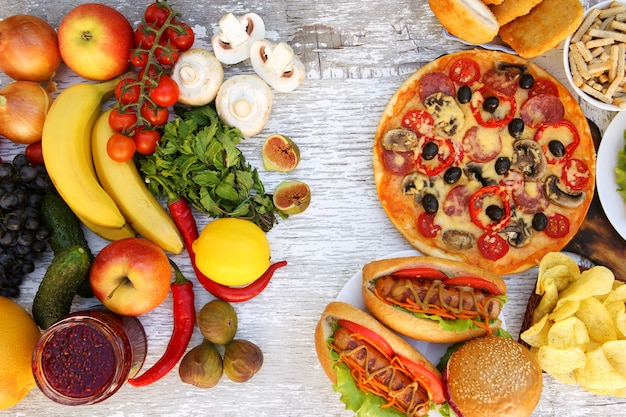 Fastfood and healthy food on old white wooden table. concept choosing correct nutrition or of junk eating. top view.