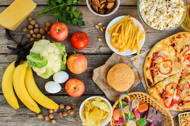 Fastfood and healthy food on old wooden surface. concept choosing correct nutrition or of junk eating. top view.