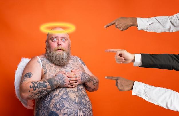 수염 문신과 날개를 가진 뚱뚱한 두려워하는 남자는 천사처럼 행동합니다