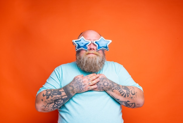 あごひげの入れ墨とサングラスをかけた太った驚いた男は何かに驚いています