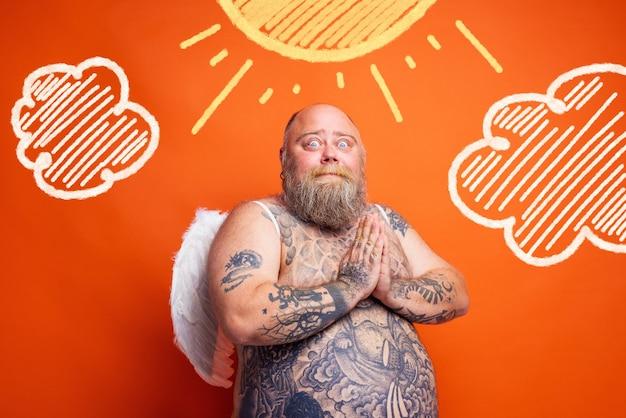あごひげの入れ墨と翼を持つ太った驚いた男は天使のように振る舞います