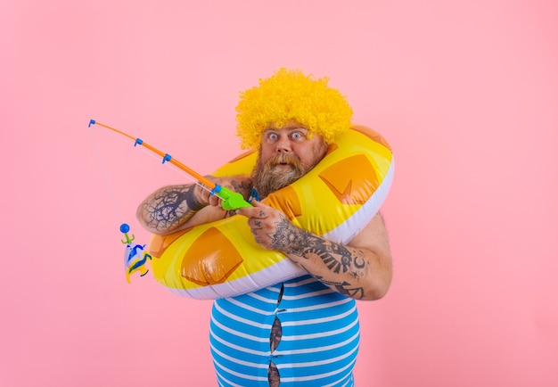 Fat amazed man with wig in head plays with the fishing rod