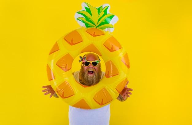 頭にかつらを持った太った驚いた男は、ドーナツの救命浮輪と一緒に泳ぐ準備ができています