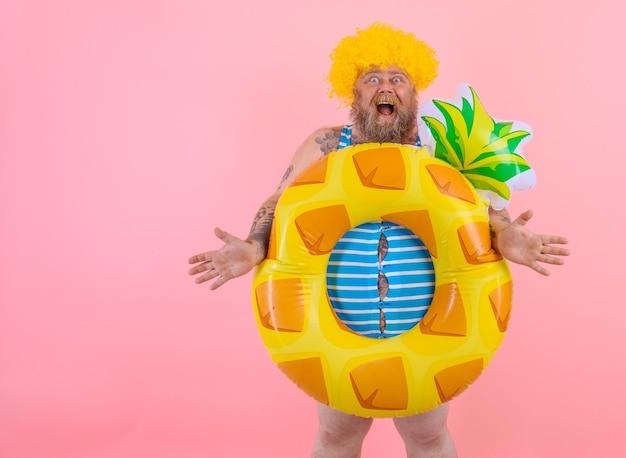 머리에 가발을 쓴 뚱뚱한 놀란 남자가 도넛 구조원과 함께 수영할 준비가 되었습니다.