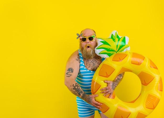 머리에 가발을 쓴 뚱뚱한 놀란 남자가 도넛 구조원과 함께 수영할 준비가 되었습니다