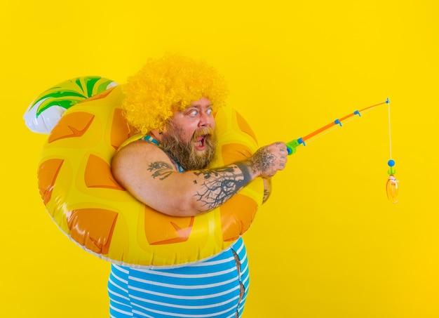 머리에 가발을 쓴 뚱뚱한 놀란 남자가 낚싯대를 가지고 노는 모습
