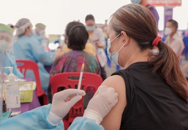 뚱뚱한 아시아 노인 여성은 현장 병원에서 의료진과 함께 코로나 바이러스 covid 예방 접종을 갔다