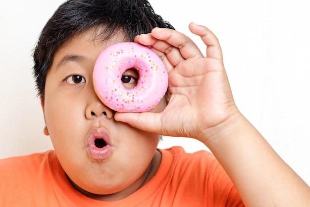 Толстый азиатский мальчик держит пончик глазированный клубникой