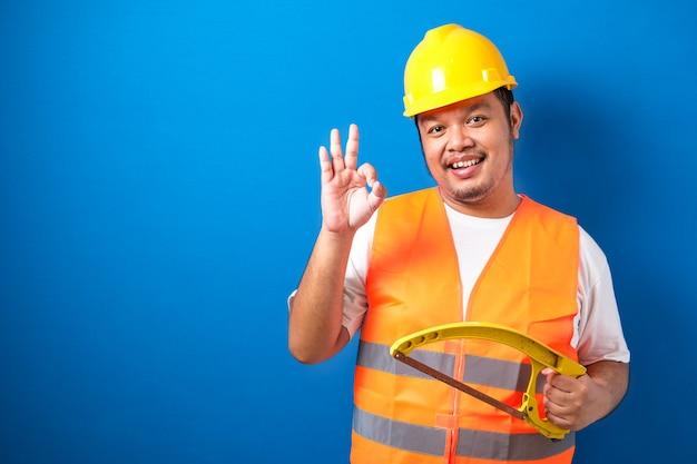 オレンジ色の安全ベストとヘルメットを身に着けている太ったアジアの建設労働者が弓のこを持っている間大丈夫な兆候を示しています