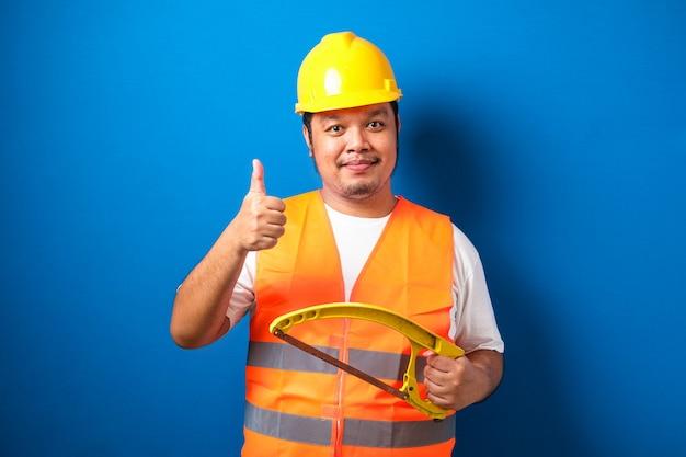 オレンジ色の安全ベストとヘルメットを身に着けている太ったアジアの建設労働者は、弓のこを保持しながら親指を立てるサインを示しています