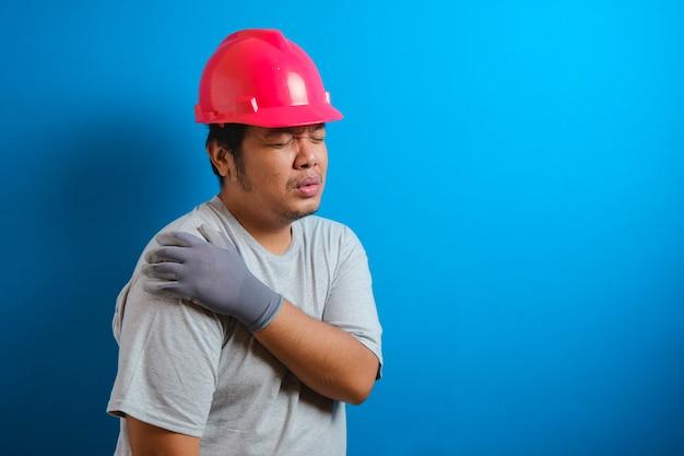 赤いヘルメットをかぶった太ったアジア人の男は、肩に痛みを感じます。男は痛みに耐えながら肩を抱える