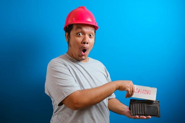 赤いヘルメットをかぶった太ったアジア人の男は、財布に稼ぎを言う何かを入れている間、カメラを見てショックを受けました。男は給料の一部を節約するために取っておこうというジェスチャーを示した