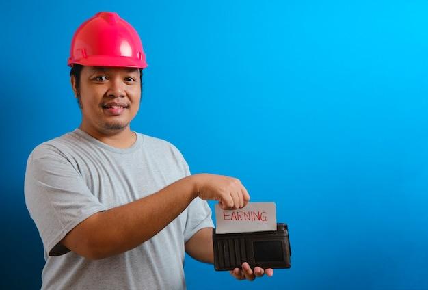 赤いヘルメットをかぶった太ったアジア人の男が、財布に稼ぎを告げる何かを入れている間、カメラに微笑みかけます。男は給料の一部を節約するために取っておこうというジェスチャーを示した