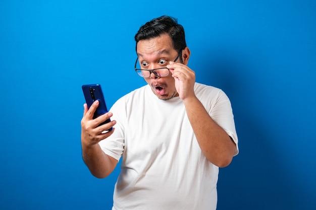 白いtシャツを着た太ったアジア人の男は、スマートフォンから受け取った良いニュースに驚いているようです。男性はスマートフォンで眼鏡を転がしながら、眼球突出でショックを受けた動きを見せます
