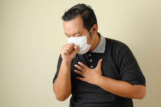 Fat asian guy wearing a mask is coughing while closing his mouth using his hands, he is feeling unwell. symptoms of corona virus disease