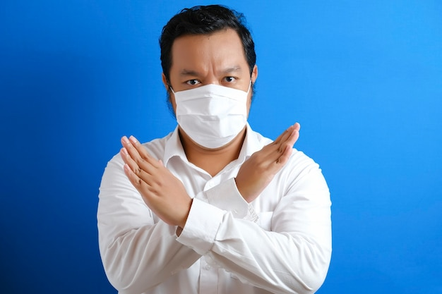A fat asian man wearing a mask to prevent transmission of the corona virus, by hand symbolizing stop gesture