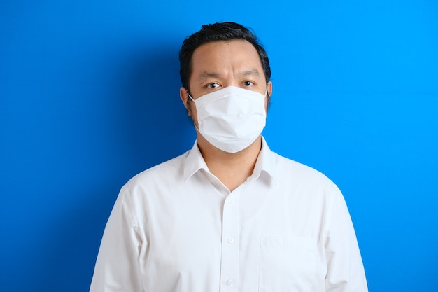 A fat asian man wearing a mask to prevent transmission of the corona virus