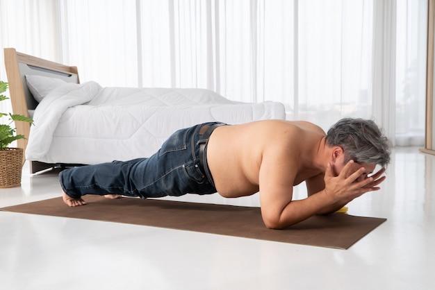 Толстые азиатские мужчины стараются сделать доски решительно и изо всех сил стараются похудеть.