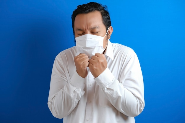 Fat asian men wearing masks feel unwell. body gestures indicate fever. blue background