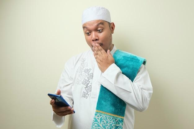뚱뚱한 아시아 이슬람 남성들은 스마트폰에서 받은 좋은 소식에 놀란 것처럼 보인다