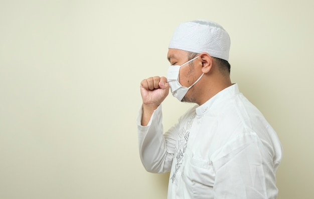 マスクを身に着けている太ったアジアのイスラム教徒の男性は、彼の手を使用して彼の口を閉じている間咳をしている