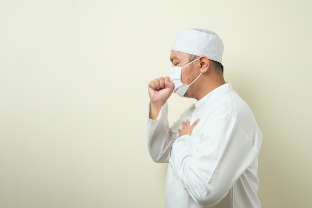Fat asian muslim men wearing a mask is coughing while closing his mouth using his hands