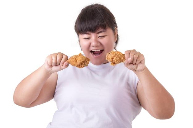 Жирная азиатская женщина, держащая и едят жареный цыпленок